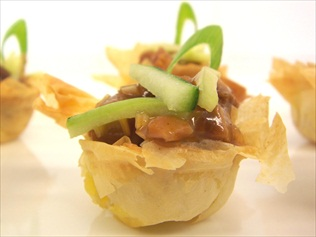 Duck with hoisin sauce in filo pastry baskets. Perfect canape for a light bite on the hoof